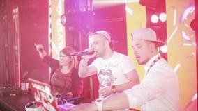 DJ que gira na plataforma giratória no partido no clube noturno spotlights Menina e menino de Mc video estoque