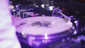 DJ que hace girar en la placa giratoria en partido en club nocturno Proyectores púrpuras holidays almacen de metraje de vídeo