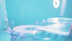 DJ que hace girar, mezcla en la placa giratoria en partido en club nocturno cheering estroboscópico holidays metrajes