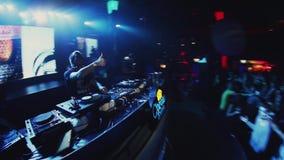DJ que hace girar y que baila en la placa giratoria en partido en club nocturno iluminaciones muchedumbre metrajes