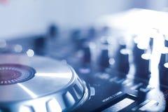 DJ que juega m?sica en el primer y las mezclas del mezclador la pista en el club nocturno fotos de archivo libres de regalías