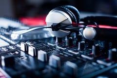 DJ que juega m?sica en el primer y las mezclas del mezclador la pista en el club nocturno foto de archivo