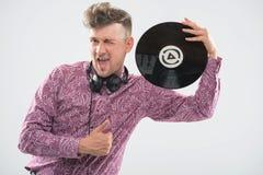 DJ que presenta con el disco de vinilo y el pulgar para arriba Imagen de archivo libre de regalías
