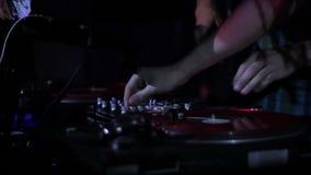 DJ que risca registros de vinil e que mistura nas plataformas em um disco no clube noturno filme