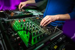 DJ`s hands at the music mixer at a party. Playing some fine songs for the guests color toned image stock photos