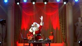 DJ Santa Claus die omhoog één of andere Kerstmisgebeurtenis mengen stock video