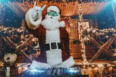 Merry disco party. DJ Santa Claus in luminous glasses and headphones holds a party near his house decorated with lights. Christmas songs and music stock images
