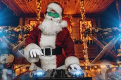 Fiery dj santa. DJ Santa Claus in luminous glasses and headphones holds a party near his house decorated with lights. Christmas songs and music stock images