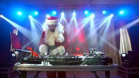 DJ Santa Claus mixing up some Christmas event. Disco light around fun, colorful atmosphere. Musical New Year stock video footage