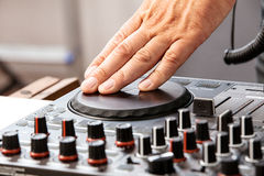 DJ is scratching. Dj concept showing hand on a console while scratching the disc Royalty Free Stock Photography