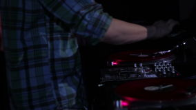 DJ scratching vinyl records and mixing on the Decks at a disco in Nightclub. Full HD stock video footage