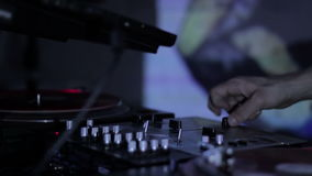 DJ scratching vinyl records and mixing on the Decks at a disco in Nightclub loop video. DJ scratching vinyl records and mixing on the Decks at a disco in stock video footage