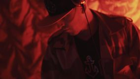 DJ in snapback and headphones playing music on turntable in red lights close up. DJ in snapback cap and headphones playing music on turntable in red lights close stock video