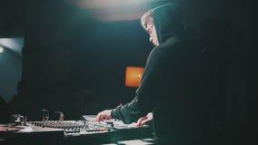 Dj som spelar musik på blandareslutet upp och blandningar spåret i nattklubben på partiet lager videofilmer