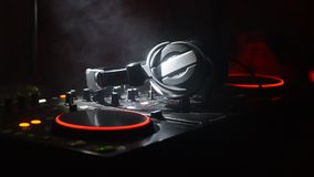 DJ Spinning, Mixing, and Scratching in a Night Club, Hands of dj tweak various track controls on dj`s deck, strobe lights and fog,. Selective focus, close up stock footage