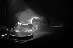 DJ Spinning, Mixing, and Scratching in a Night Club, Hands of dj tweak various track controls on dj's deck, strobe lights and fog, Stock Photo