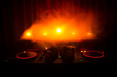 DJ Spinning, Mixing, and Scratching in a Night Club, Hands of dj tweak various track controls on dj's deck, strobe lights and fog, Stock Images
