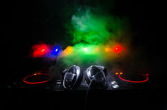 DJ Spinning, Mixing, and Scratching in a Night Club, Hands of dj tweak various track controls on dj's deck, strobe lights and fog, Royalty Free Stock Photography
