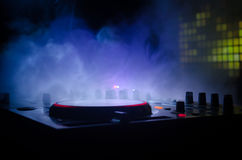 DJ Spinning, Mixing, and Scratching in a Night Club, Hands of dj tweak various track controls on dj's deck, strobe lights and fog, Royalty Free Stock Image