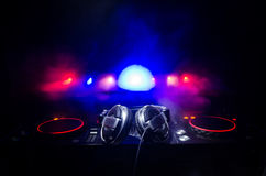 DJ Spinning, Mixing, and Scratching in a Night Club, Hands of dj tweak various track controls on dj's deck, strobe lights and fog, Royalty Free Stock Images