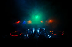 DJ Spinning, Mixing, and Scratching in a Night Club, Hands of dj tweak various track controls on dj's deck, strobe lights and fog, Royalty Free Stock Photo