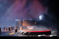DJ Spinning, Mixing, and Scratching in a Night Club, Hands of dj tweak various track controls on dj's deck, strobe lights and fog, Stock Image