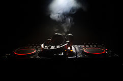 DJ Spinning, Mixing, and Scratching in a Night Club, Hands of dj tweak various track controls on dj's deck, strobe lights and fog, Royalty Free Stock Photos