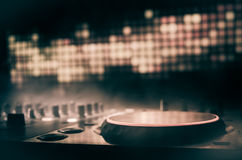 DJ Spinning, Mixing, and Scratching in a Night Club, Hands of dj tweak various track controls on dj's deck, strobe lights and fog. Selective focus, close up Stock Photography