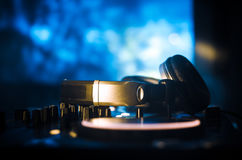 DJ Spinning, Mixing, and Scratching in a Night Club, Hands of dj tweak various track controls on dj's deck, strobe lights and fog Royalty Free Stock Images