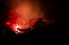 DJ Spinning, Mixing, and Scratching in a Night Club, Hands of dj tweak various track controls on dj's deck, strobe lights and fog Royalty Free Stock Photos