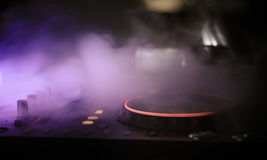DJ Spinning, Mixing, and Scratching in a Night Club, Hands of dj tweak various track controls on dj's deck, strobe lights and fog Stock Photography