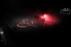 DJ Spinning, Mixing, and Scratching in a Night Club, Hands of dj tweak various track controls on dj's deck, strobe lights and fog Royalty Free Stock Image