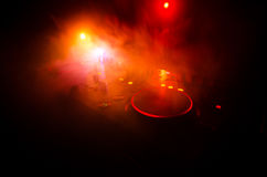 DJ Spinning, Mixing, and Scratching in a Night Club, Hands of dj tweak various track controls on dj's deck, strobe lights and fog Royalty Free Stock Photo