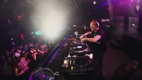 Dj spinning, mixing at turntable on party in crowded nightclub. Spotlights. stock video