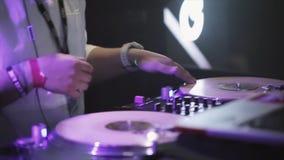 Dj spinning at turntable on party in nightclub. Cheering. Purple spotlights. stock video footage
