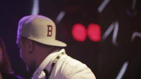 Dj spinning at turntable on party in nightclub. Girl dance. Purple spotlights. stock video footage