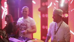Dj spinning at turntable on party in nightclub. Illuminations. Mc girl and boy. stock video