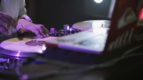 Dj spinning at turntable on party in nightclub. Laptop. Spotlights. Tattoo. stock footage