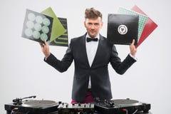 DJ stoi obok w smokingu pokazuje jego winylowych rejestry Fotografia Stock