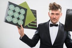 DJ stoi obok w smokingu pokazuje jego winylowych rejestry Zdjęcie Royalty Free