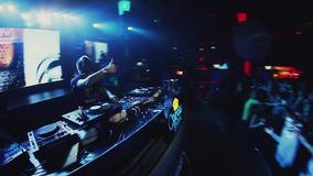 Dj taniec przy turntable na przyjęciu w klubie nocnym i przędzalnictwo złudzenie tłum zbiory