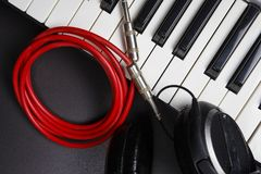 DJ Tools. Musical instruments close-up on black background. Synthesizer, headphones and cable. Midi keys and jack cable. Stock Photography