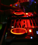Dj at the turntables. Blurry image of a dj mixing sound at a dancehall party Royalty Free Stock Photography