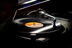 Dj turntables needle cartridge on black vinyl record with music. Close up, focus on turntable and audio disc record. Dj turntables needle cartridge on black Stock Image