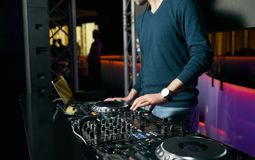 DJ with Turntables playing music at mixer. Dj mixing indoor at party festival Stock Images