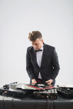 DJ in tuxedo looking at his vinyl records standing Stock Images