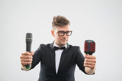 DJ in tuxedo posing with two microphones Stock Image
