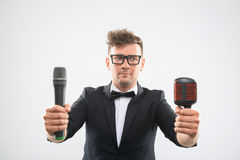 DJ in tuxedo posing with two microphones Stock Images