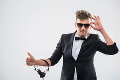 DJ in tuxedo showing his thumb up standing by. Half-length portrait of stylish handsome DJ in tuxedo and sunglasses showing his thumb up as sign OK with Stock Image