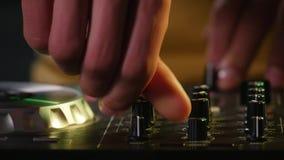 DJ twirls regulators on the equipment.  Stock Photos
